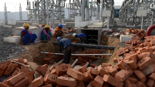 Indian labourers work at the upcoming power sub station at the Gujarat International Finance Tec-City (GIFT City) on the outskirts of Gandhinagar, some 30 kms from Ahmedabad on June 26, 2014.